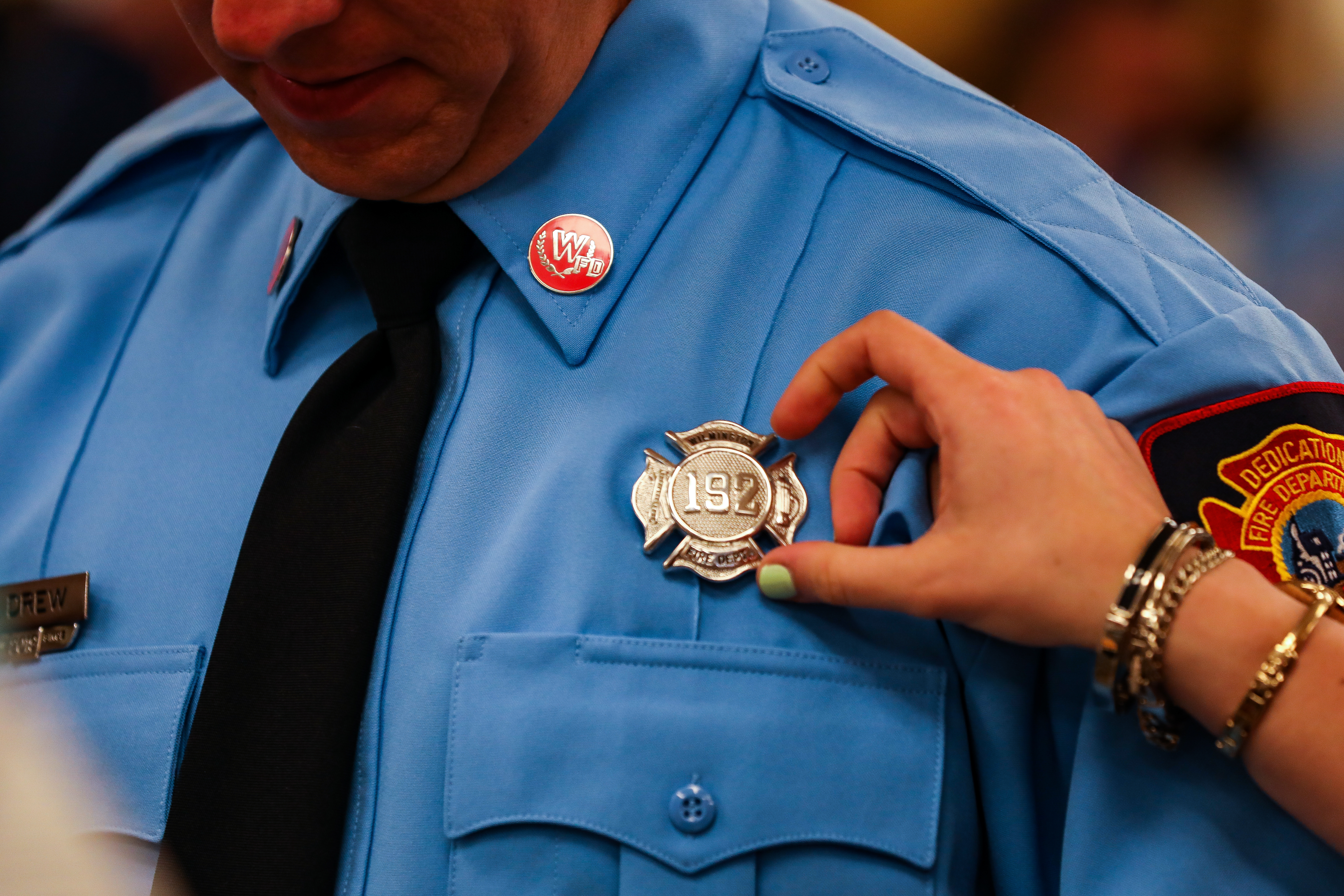 Wilmington fire fighter receives badge at graduation.